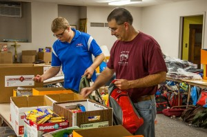 Oskaloosa School Board members Charlie Comfort (left) and Tom Richardson (right) help fill backpacks.