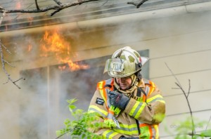Oskaloosa Fire Captain Dave Christenson prepares to attack flames leaping from a second story window.
