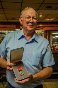 Gary Lindgren displays the Broze Star awarded to his father Elmer Lindgren posthumously.