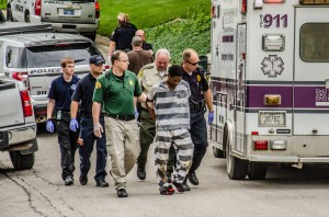 Martell Lamar Tillman-Hollinshed is lead to an awaiting ambulance following his attempt to flee from custody Wednesday.