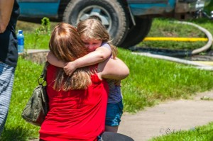 Christina Graham (left) and her daughter Gracie (right) hug each other just outside of their destroyed home.