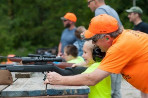 Jeff Vanderbeek, with Mahaska County Pheasants Forever, (in orange), helps a local youth 'Young Guns' participant during Saturday's inaugural event.