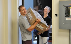 Members of the Oskaloosa Indian Football Team helped Label Shopper unload two truckloads merchandise as they moved into Penn Central Mall today. Pictured above are Jimmy Brown (left) and Andy Sterner (right). Label Shopper offers brand name designer fashions for 25-70 percent off the department store price. The Oskaloosa store is the first Iowa store in the chain.  It will offer women's and men's clothing, shoes, accessories and famous-label handbags. The store will open August 1 in time for the back-to-school tax-free holiday.