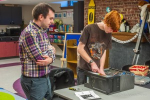 Oskaloosa Library Director William Ottens (left) and Ethan Doak (right) took part in Tech Tear Down Monday night.