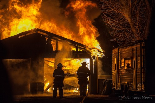 Oskaloosa firefighters Tim Nance and Scott Howard tackle the flames Sunday evening.