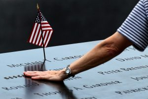 A woman places her hand over a name on the memorial at the National September 11 Memorial and Museum in Lower Manhattan in New York City, U.S., September 9, 2016. REUTERS/Brendan McDermid