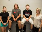 L-R: Athletic Trainer Laura Norberg, Senior Blake Van Veldhuizen, Senior Brandt Brown, and Physical Therapist Carol Kelderman smile in front of the newly renovated taping table