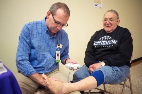 Dr. Beers checks blood flow in Elmer Stahl's legs at a free screening during Saturday's Diabetes Fair inside Penn Central Mall.