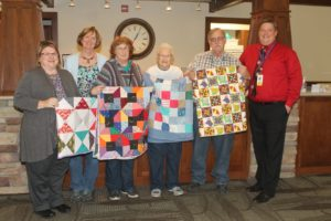 Shown at the Mahaska Health Partnership Hospice Serenity House with quilts donated by the Get 'R Done Quilting Group of Barnes City are, from left: MHP Hospice Coordinator Kim Stek, Jan Beck, Kristi Ehle, Lareta Sanders, David L. Fry, and MHP Home Health/Hospice and Public Health Director Travis Smith.