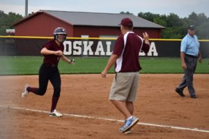 Josie Bunnell rounds 3rd, congratulated by Coach Harms on her way to home plate after hitting a Grand Slam  (photo by Wendy Van Roekel)