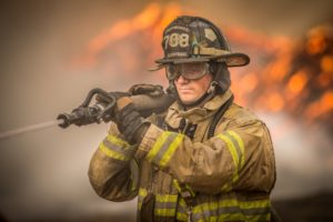 Oskaloosa firefighter Adam Haroldson tackles the flames at the B&B Bedding fire on Saturday afternoon.