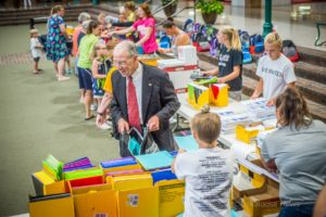 Senator Chuck Grassley helps to fill a backpack at Penn Central Mall this past week.