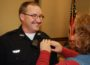 Oskaloosa's newest police officer, James Arment has his badge pinned on him by his wife during Monday's city council meeting. (Oskaloosa Police Department Photo)