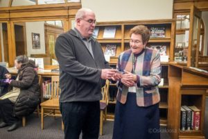 Bryan Johnson with Friends of the Oskaloosa Public Library presents Susan Hasso (right) with a lifetime card.